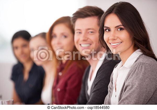 mulher, dela, sentando, câmera, pessoas, jovem, seminar., enquanto, outro, atraente, atrás de, sorrindo, fila - csp18544580