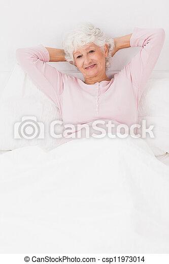 mulher sorridente, cama - csp11973014