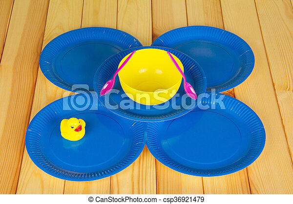 Multi-colored disposable plates and spoons against the backdrop pale wood. - csp36921479 & Multi-colored disposable plates and spoons against the... picture ...