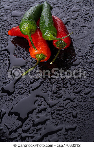Multi-coloured peppers with tails in camera. - csp77063212