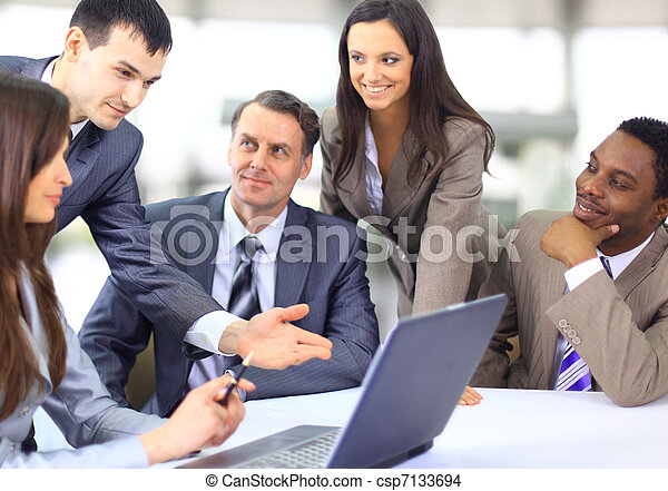 Multi ejecutivos de negocios étnicos en una reunión discutiendo un trabajo - csp7133694