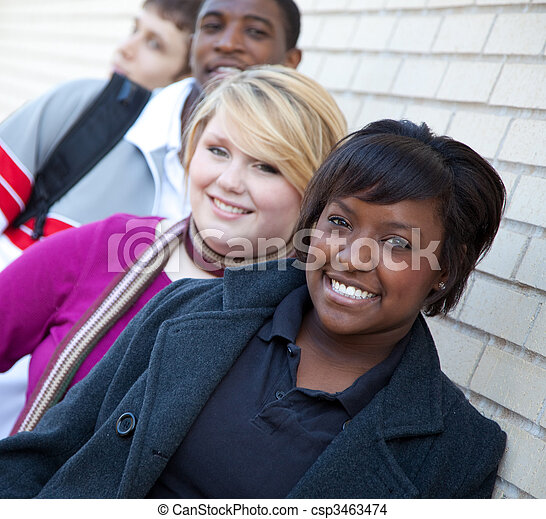 Multi-racial college students against a brick wall - csp3463474