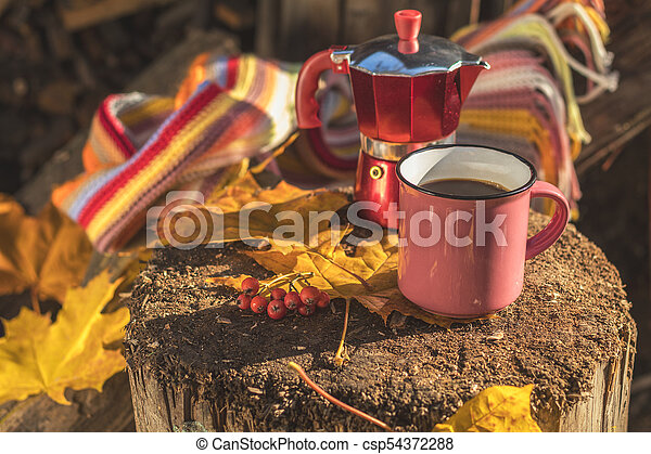 Multicolored scarf, cup of coffee, red coffee maker, yellow maple and oak leaves on the wooden board. Bright autumn background. Sunlight, copy space. - csp54372288