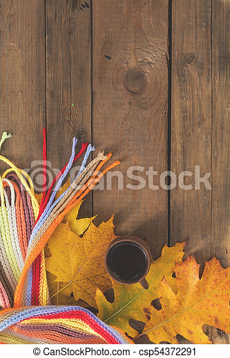 Multicolored scarf, cup of coffee, yellow maple and oak leaves on the wooden board. Bright autumn background. Sunlight, copy space, top view - csp54372291