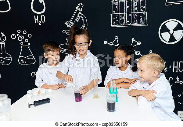 Multiracial diverse kids with test tubes studying chemistry at school laboratory - csp83550159