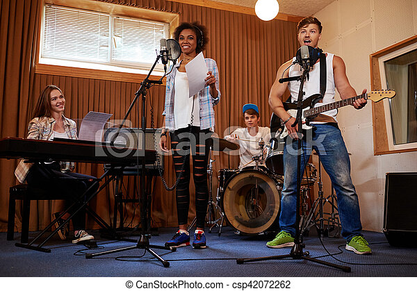 Multiracial music band performing in a recording studio - csp42072262
