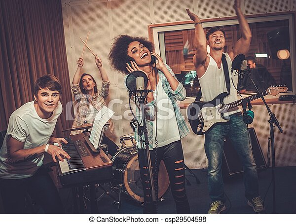 Multiracial music band performing in a recording studio  - csp29504598