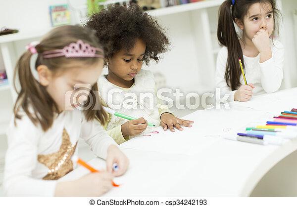 Niños multiraciales dibujando en la sala de juegos - csp34242193