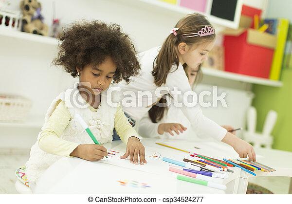 Niños multiraciales dibujando en la sala de juegos - csp34524277