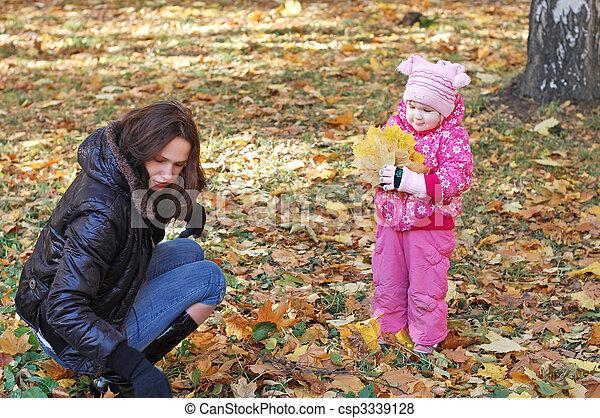 Mum with a daughter walk in autumn park - csp3339128