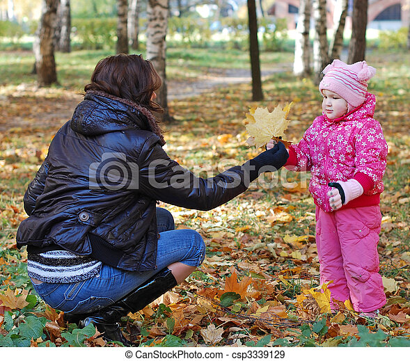Mum with a daughter walk in autumn park - csp3339129