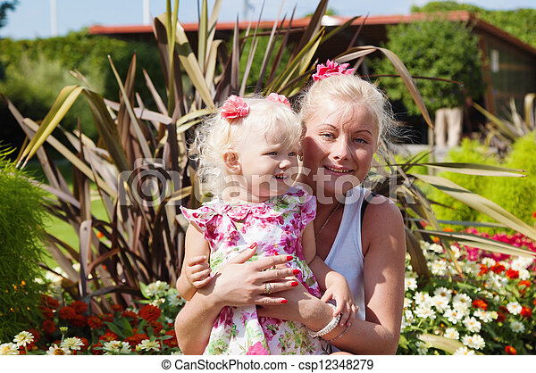 Mum with a small daughter among flowers in park - csp12348279