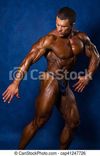 a6ece65ebaf Muscular athletic man in a pose on a blue background. bodybuilder ...