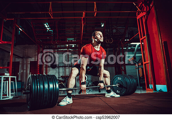95964a0c5318 Muscular fitness man doing deadlift a barbell in modern fitness center.  functional training. snatch exercise. sumo style.