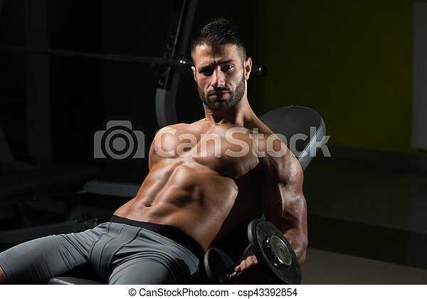 Muscular Man Exercising Biceps With Dumbbell - csp43392854