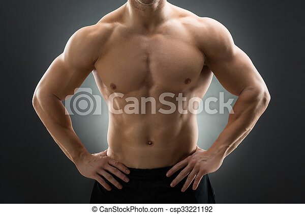 Muscular man standing with hands on hip. Midsection of muscular man ...