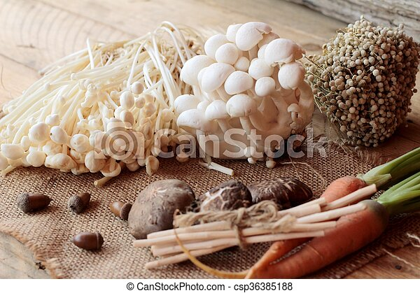 Mushrooms and vegetables on wood background. - csp36385188