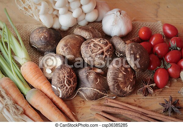 Mushrooms and vegetables on wood background. - csp36385285