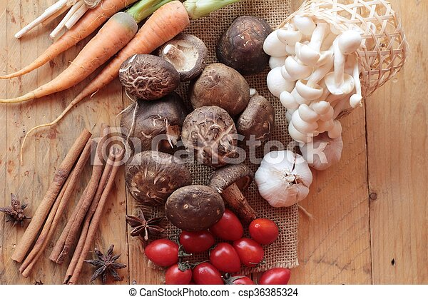 Mushrooms and vegetables on wood background. - csp36385324