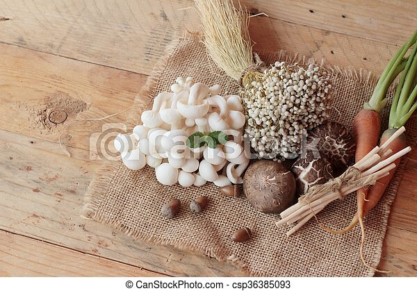 Mushrooms and vegetables on wood background. - csp36385093