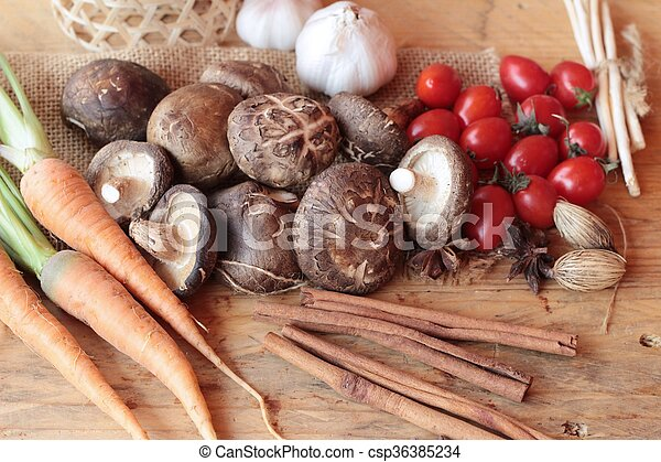 Mushrooms and vegetables on wood background. - csp36385234