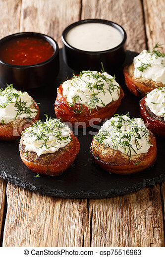 Mushrooms stuffed with cream cheese wrapped in bacon close-up on a plate. vertical - csp75516963