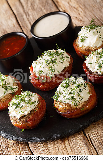 mushrooms wrapped in bacon and stuffed with cream cheese with greens closeup on a plate. vertical - csp75516966