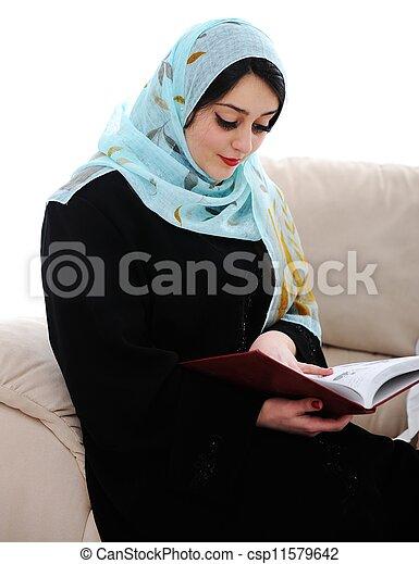muslim arabic woman reading book on sofa