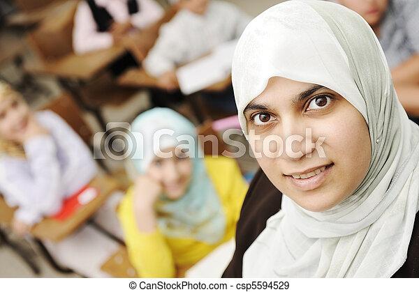 Muslim female teacher in classroom with children pupils (students) - csp5594529