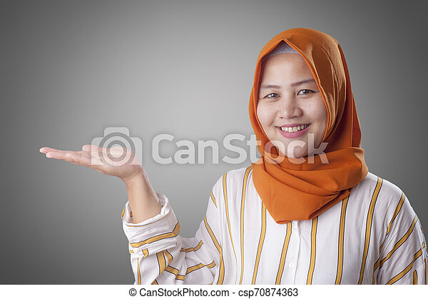 Muslim Lady Presenting Something on Her Side with Copy Space - csp70874363