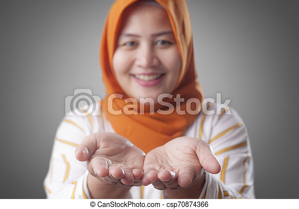 Muslim Lady Shows Something in Her Empty Hands - csp70874366