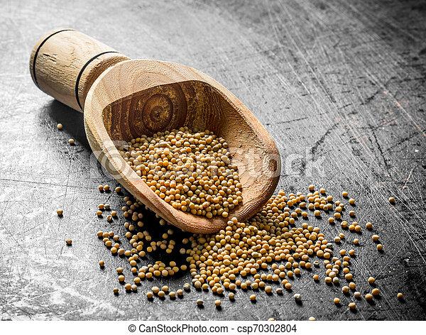 Mustard in a wooden scoop. - csp70302804