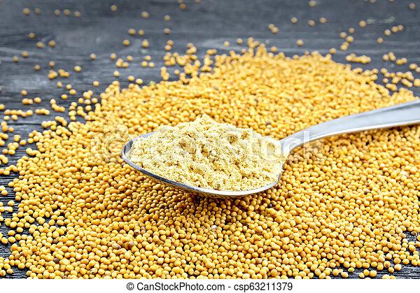 Mustard powder in spoon on black board - csp63211379