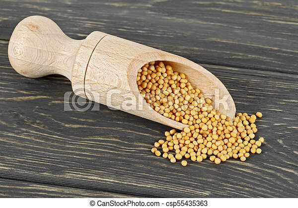 Mustard seeds in wooden scoop, wooden background - csp55435363