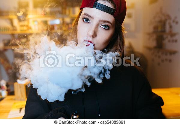 nő, meglehetősen, shop., vape, sapka, fiatal, cigaretta, piros, dohányzik, elektronikus, style., hip-hop, closeup. - csp54083861