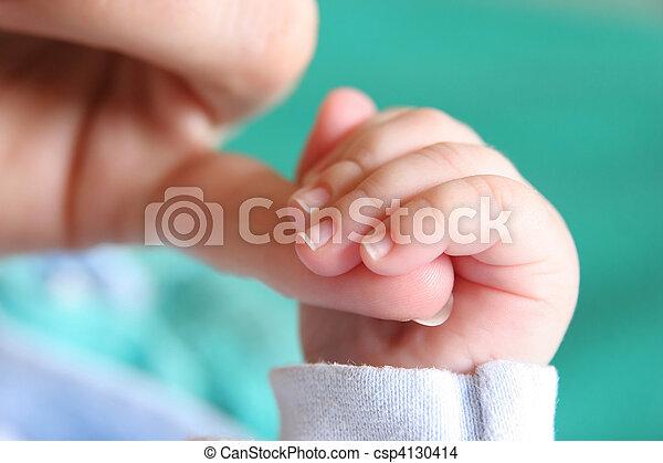 La mano de bebé recién nacida agarrada del dedo de la madre - csp4130414
