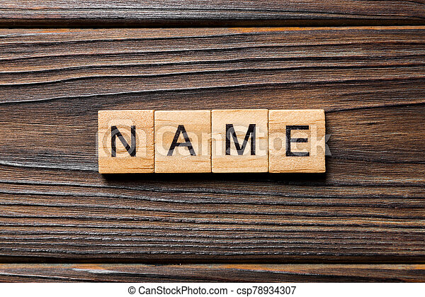 NAME word written on wood block. NAME text on wooden table for your desing, concept - csp78934307