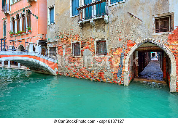 Narrow canal along old brick houses. Venice, Italy. - csp16137127