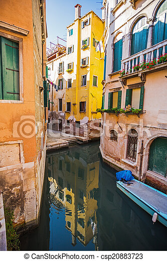 Narrow canal among old colorful brick houses in Venice - csp20883723