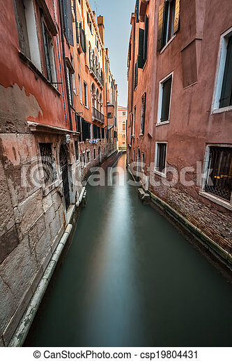 Narrow Canal Among Old Colorful Brick Houses in Venice, Italy - csp19804431