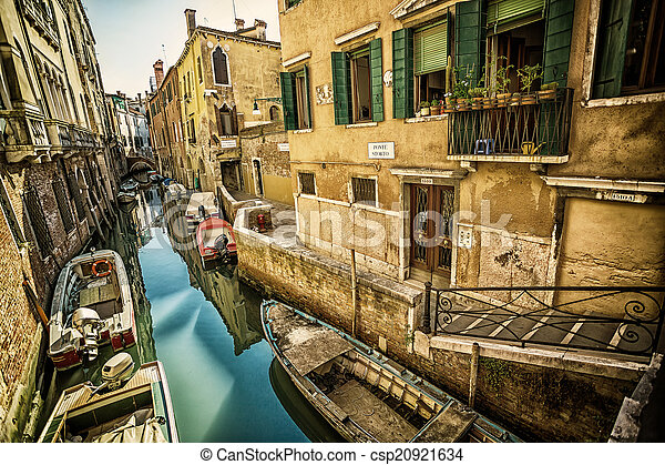 Narrow canal among old colorful brick houses in Venice - csp20921634
