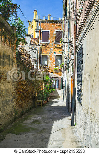 Narrow canal among old colorful brick houses in Venice - csp42135538