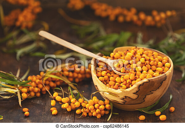 Natural, organic sea buckthorn berry in bowl on dark wooden background - csp62486145
