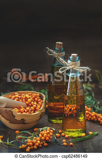 Natural, organic sea-buckthorn berry in bowl and sea buckthorn oil in glass vintage bottle - csp62486149