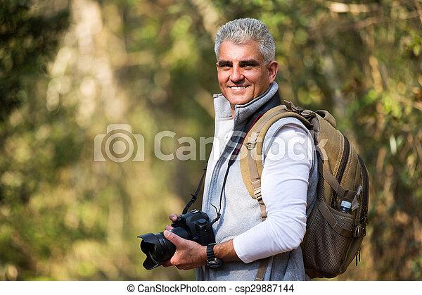 Hombre de mediana edad tomando fotos en la naturaleza - csp29887144