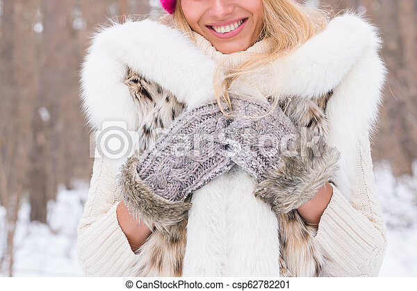 Nature, fashion and people concept - Close up portrait of beautiful young woman in winter park with snow - csp62782201