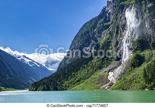 Nature landscape scenery view of a waterfall in Austria, located in the idyllic Zillertal Alps Nature Park - csp71774657