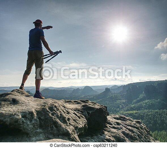 Nature photographer hold tripod with camera. Man at sunrise - csp63211240