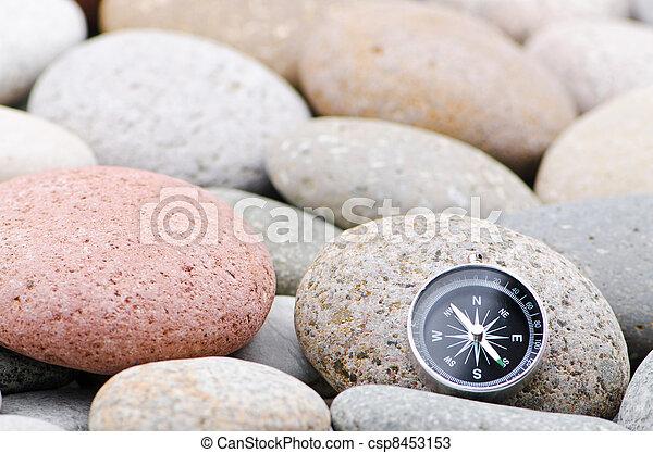 Navigation compass on stone pebbles - csp8453153