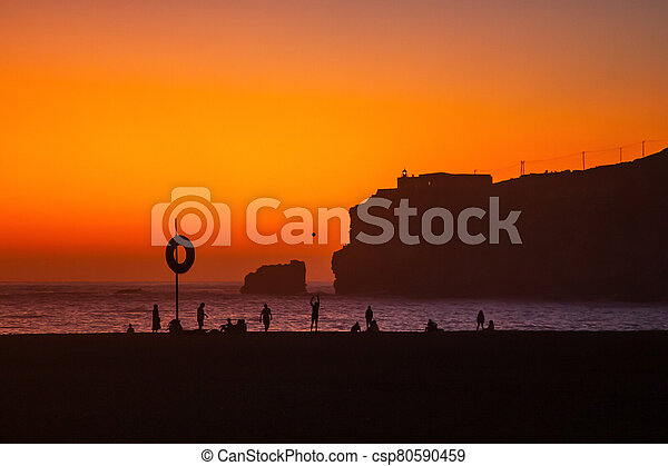 Nazare, Portugal: Amazing orange sunset over Atlantic Ocean and people relaxing on the beach. Lighthouse and Fort of Sao Miguel visible on the high cliff. - csp80590459